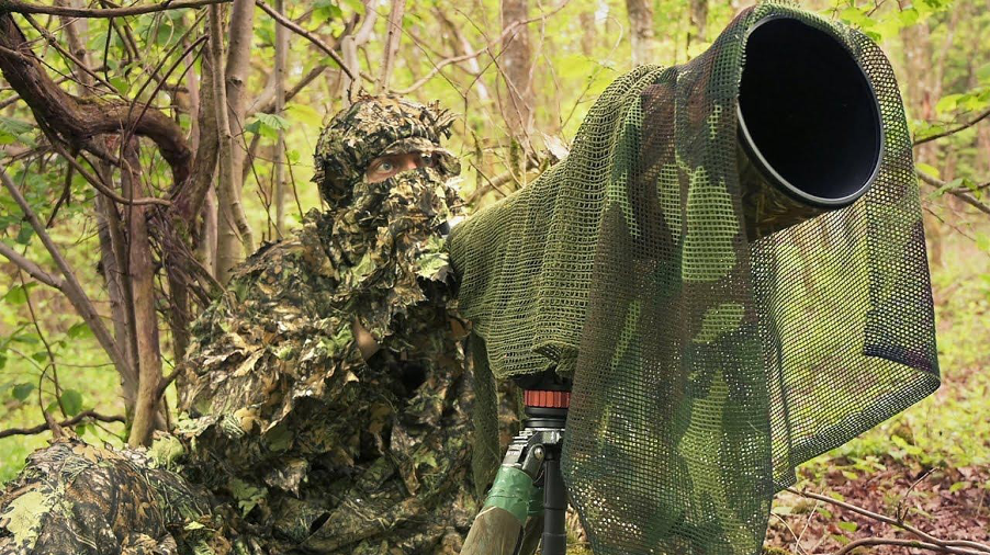 A person in a woodland wearing full camouflage holding a camera with a telephoto lens